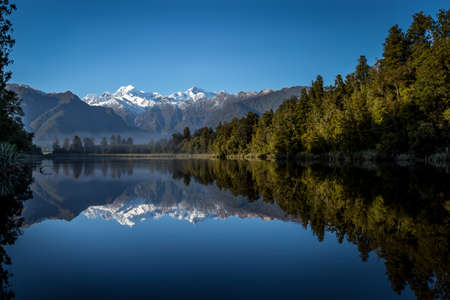 new zealand: morning reflection of snowy mountains on lake