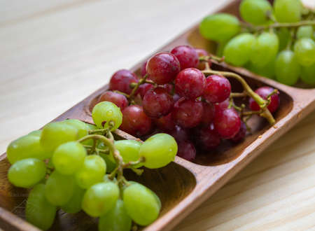 fresh red and green grapes in wooden container
