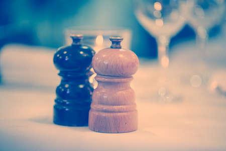pepper grinder: salt and pepper grinder set on table prepared for luxurious dinner. Instagram filtered effect. Stock Photo