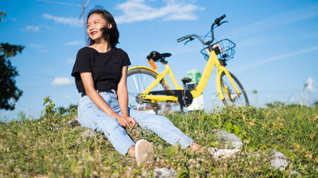 Happy young asian girl with yellow bicycle at park .