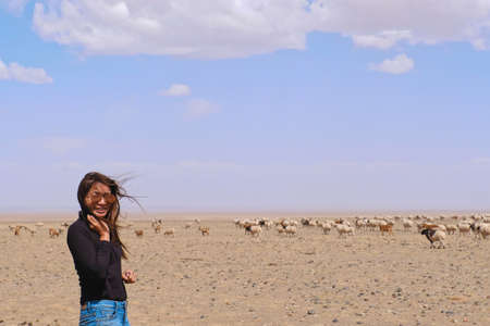 Asia woman wear jean at gobi desert Mongolian with goat and sheep background and nice sky at Mongolia