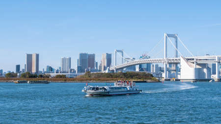 November 17,2019 : Boat drive pass Rainbow Bridge at Daiba beach famous landmark at Japan.