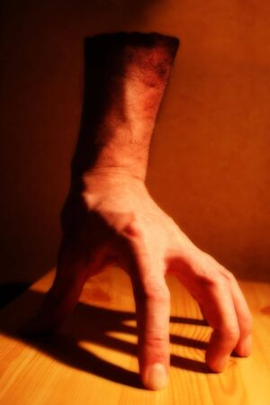 An effects image of a disembodied hand under tungsten lighting on a wooden board with a heavy shadow. Intentionally semi-blurred. Stock Photo