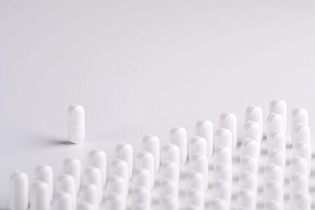 addresses: A Pill leader addresses lines of white pills Stock Photo