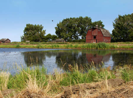 This photo features an old farmyard and it's outbuildings. Clear reflections in the lake and birds overhead. Stock Photo - 1806547