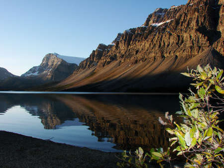 Bow Lake with first touches of sunlight on the shoreline. Includes good reflections of the mountains in the lake. Stock Photo