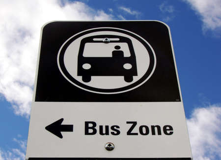 This bus sign stands against a blue sky. Arrow points left.