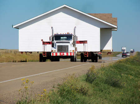 This house rolls down a highway followed by some traffic. Could be used to indicate relocation of house or office.