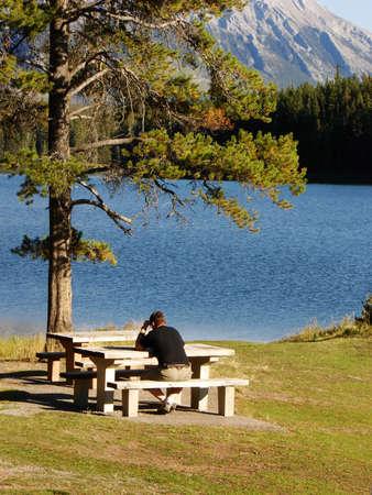 Man deep in though next to mountain lake. Stock Photo