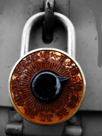 A rusty old combination lock has shallow depth of field. Could be used to illustrate forgotten combination.