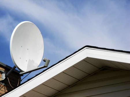 repaired: This repaired satellite dish perches on top of a house.