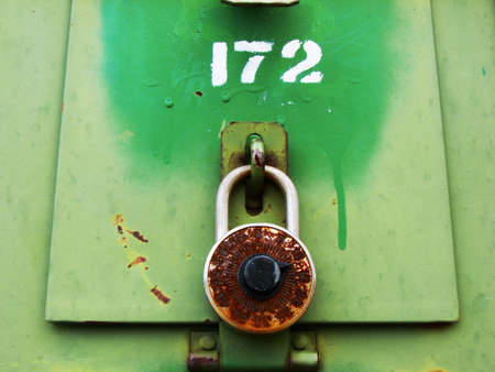 A rusty old combination lock on green mailbox. Could be used to illustrate forgotten combination. Stock Photo