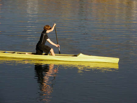 A teenager paddles a bright yellow canoe. Superb reflections from the water