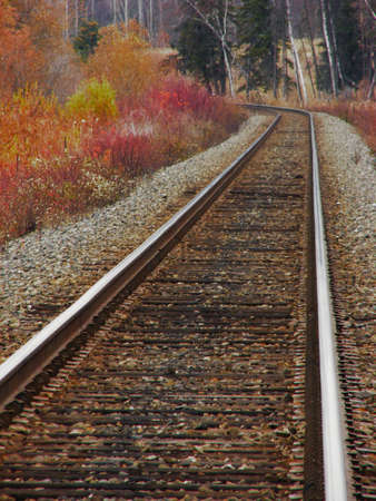 A set of deserted train tracks leads round a corner. Features vivid fall colors on the trees. Slight fog in background. Stock Photo