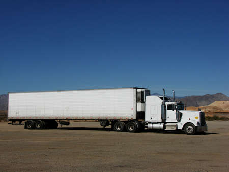 A plain white semi parked in the desert. Features loads of text space.