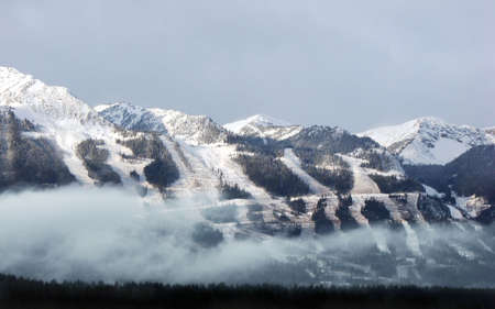A panorama of a ski hilll about to open after the first winter snows. Threatening clouds are offset by the sunlight on the peaks. Low lying clouds obscure trees in the foreground valley.