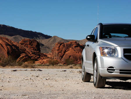A Silver car parked on a desert road. Provides loads of copy space. Interesting red rocky background