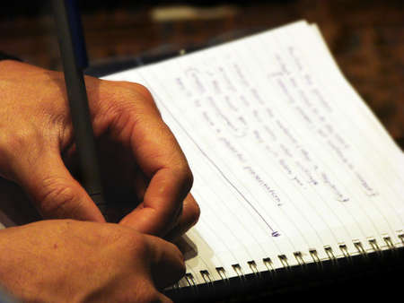A person taking notes during a conference. Conference hall lighting