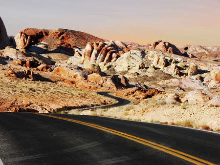This road, meanders through the red rocks of the Nevada desert towards brightly colored rocks.