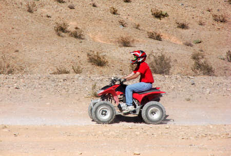 A young adult drives a vivid red atv through the red desert sand.