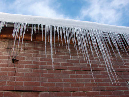 These icicles dangle infront of an aged brick building.