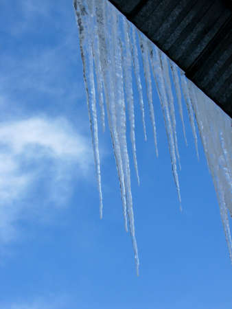 These icicles dangle from a corregated tin roof. Stock Photo