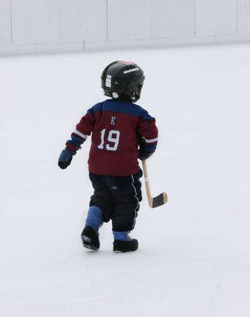 この小さな少年はひどくホッケーをプレイしたい、彼は氷スケートなしで実行します。