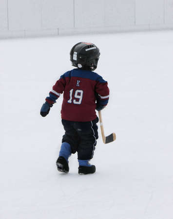 This little boy wants to play hockey so badly, hes run out on the ice without skates. Stock Photo