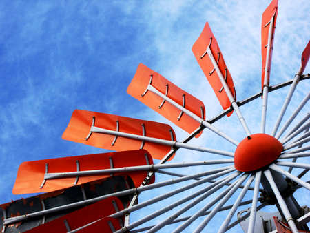 A brilliant orange windmill stands on a blue sky