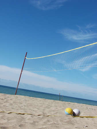 A beach volleyball court in the sand. Sea and sky featured in this unique perspective. Stock Photo