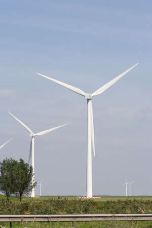 inconvenient: White wind turbine standing on open plain.