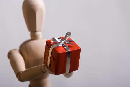 enrich: Wooden marionette presenting a red gift. Short DOF.