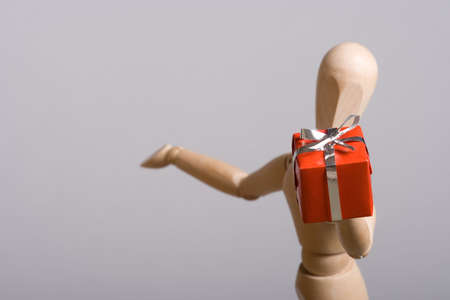 Wooden marionette presenting a red gift. Short DOF. Stock Photo - 3766646