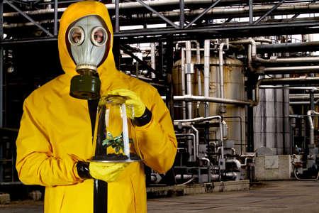 riesgo biologico: Hombre con traje de qu�mica con m�scara sosteniendo la planta en un invernadero port�til en planta qu�mica Foto de archivo
