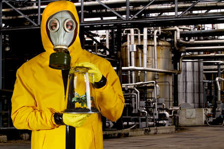 chemical hazard: Man in chemical suit with mask holding plant in a portable greenhouse at chemical plant Stock Photo