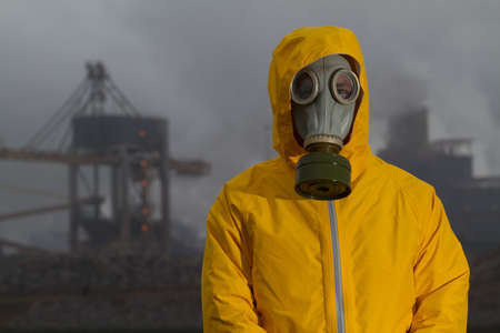 ecological disaster: Man wearing gas mask standing infront of factory. Frontal shot. Background out of focus