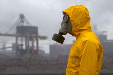 Hombre vistiendo de máscara de gas de pie delante de la fábrica. Lado un disparo. Fondo fuera de foco Foto de archivo