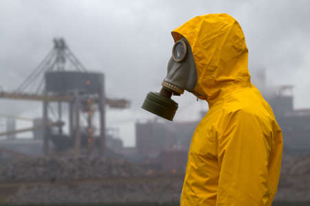 environmental safety: Man wearing gas mask standing infront of factory. Side shot. Background out of focus Stock Photo