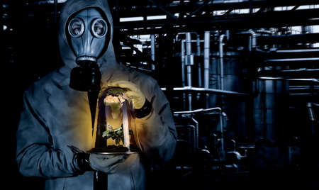toxins: Man in chemical suit with mask holding plant in a portable greenhouse at chemical plant. Earth reflecting on glass