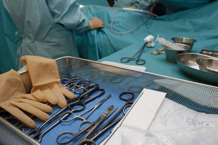 physicals: Surgical tools, with surgeons busy performing operation in background. Short DOF Stock Photo