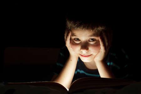 Junge Bedtime Geschichte, dunkle Foto, Schlüssel Licht, die aus Buch lesen