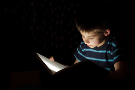 Boy reading bedtime story, dark photo, key light coming from book