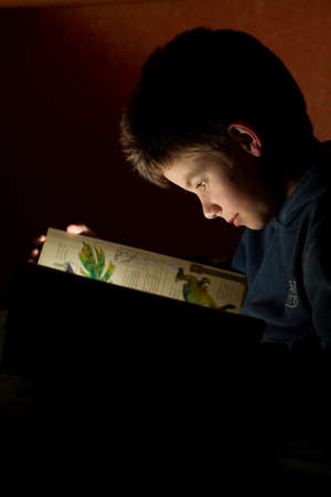 night school: Young boy reading book in bed at night. Book as only lightsource Stock Photo