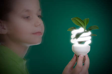 saving energy: Kid holding a compact fluorescent bulb with a leaf. Global wamring concept. On green backdrop Stock Photo