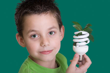 save energy: Kid holding a compact fluorescent bulb with a leaf. Global wamring concept. On green backdrop Stock Photo