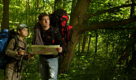 lost child: Father and son hiking in forest. Looking at map. Stock Photo