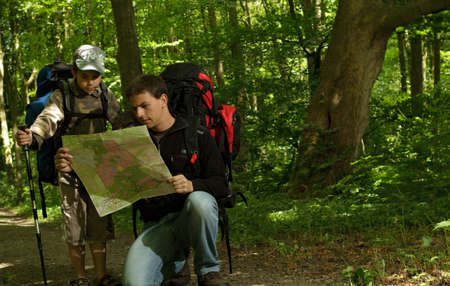 Father and son hiking in forest. Looking at map. photo