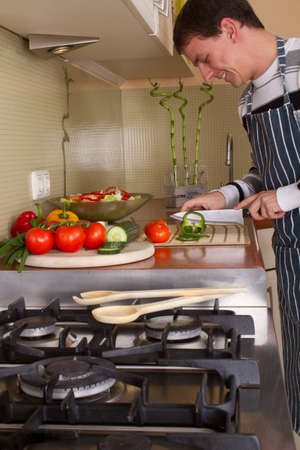 unmarried: Caucasian male preparing food in home kitchen. Lifestyle