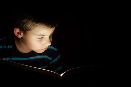 Boy reading bedtime story, dark photo, key light coming from book Stock Photo - 8723647