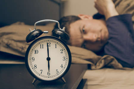despertarse: Despertador con modelo masculino en la cama en segundo plano. Profundidad de campo.